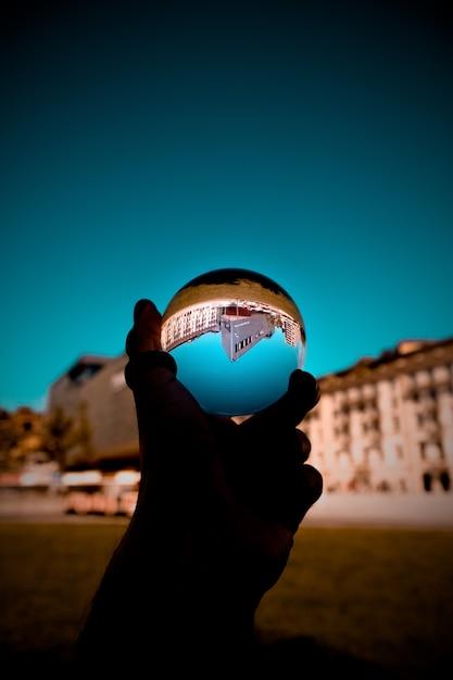 Человек держит стеклянный шар с отражением зданий и голубого неба. Бесплатные Фотографии