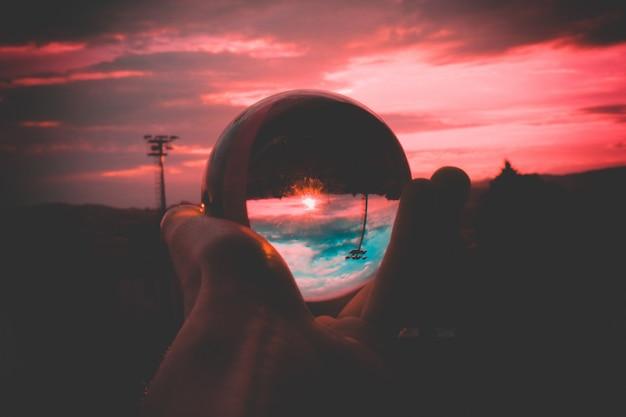 カラフルな空と美しい夕日の反射でガラス玉を握る人 無料写真