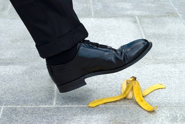 A person is going to step on a banana peel Free Photo