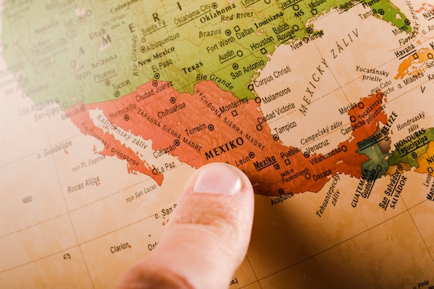 A person's finger showing Mexico city on map Free Photo