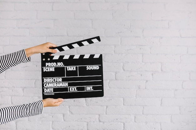 A person's hand holding clapperboard in front of brick wall Free Photo