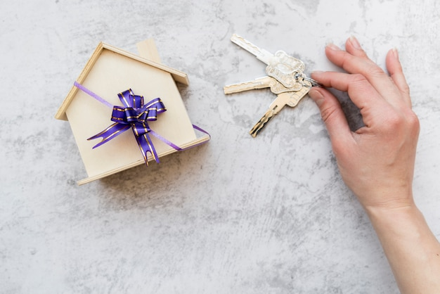 コンクリートの背景に紫の弓と木造住宅モデルの近くのキーを持っている人の手 Premium写真