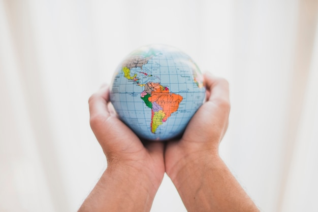 A person's hand holding small globe Free Photo