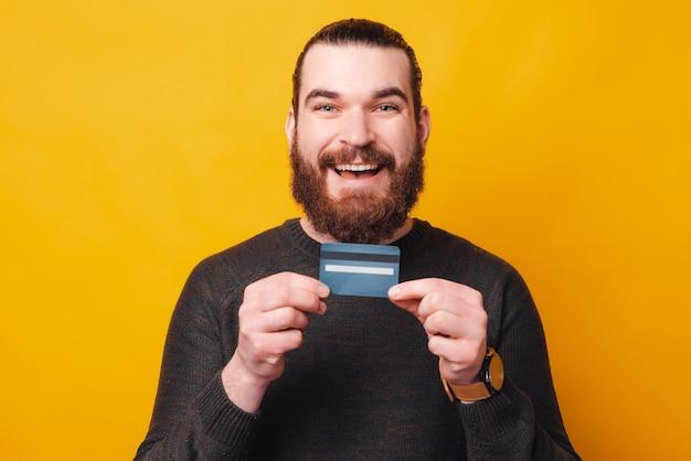 何かを買う準備ができているクレジットカードを持っているひげを生やした男の写真 Premium写真