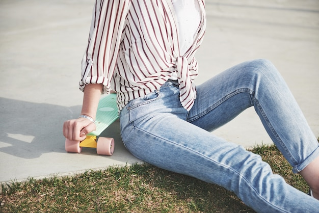 美しい髪の美しい少女の写真は、長いボードと笑顔の都会の生活にスケートボードを抱えています。 無料写真