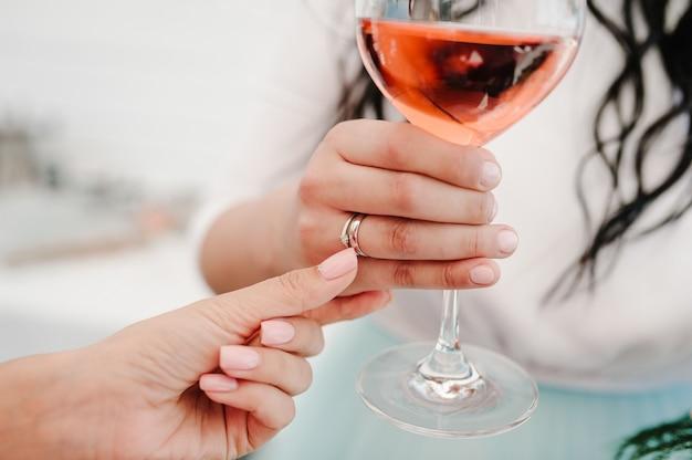 Фотография дамы, держащей бокал вина с обручальным кольцом на пальце на вечеринке Premium Фотографии