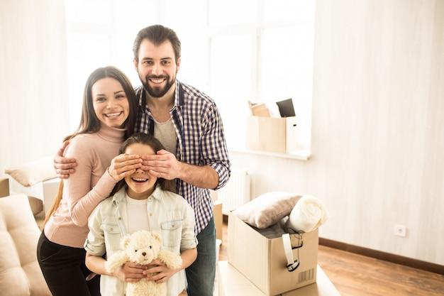 Картинка милой и веселой семьи. молодые родители держат руки на глазах у ребенка. маленькая девочка держит игрушку медведя и улыбается. Premium Фотографии