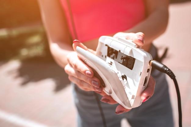 Изображение открытого игрока. есть свободное место для кассеты. девушка держит в руках это старомодное устройство. Premium Фотографии
