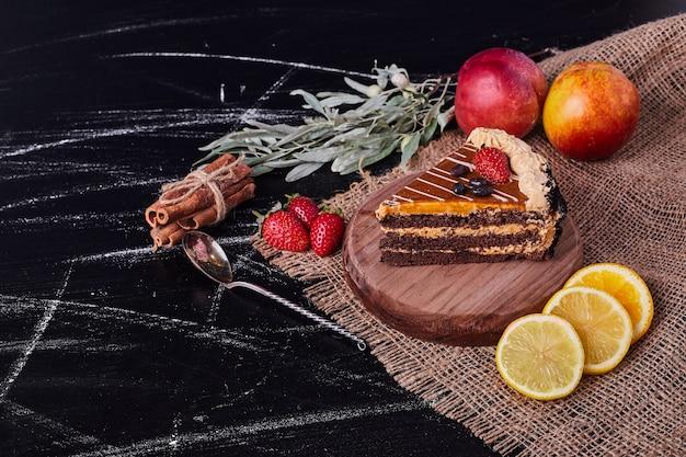 Кусок шоколадного торта на круглой деревянной тарелке с корицей и различными фруктами. Бесплатные Фотографии