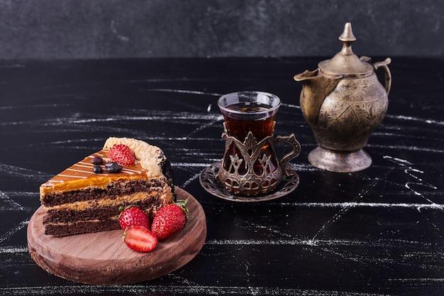 暗い背景に古典的なお茶セットとチョコレートケーキ。 無料写真