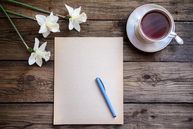ペンと白い水仙と木製の背景にお茶を一枚の紙 Premium写真
