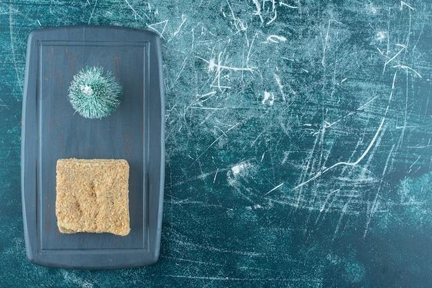 어두운 접시에 작은 크리스마스 트리와 함께 맛있는 케이크의 조각. 고품질 사진 무료 사진