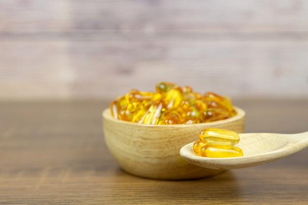Куча капсулы масла печени трески в чашке и деревянной ложке. Premium Фотографии