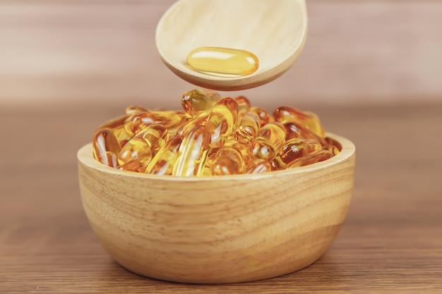 Куча капсулы масла печени трески в деревянной ложке. Premium Фотографии