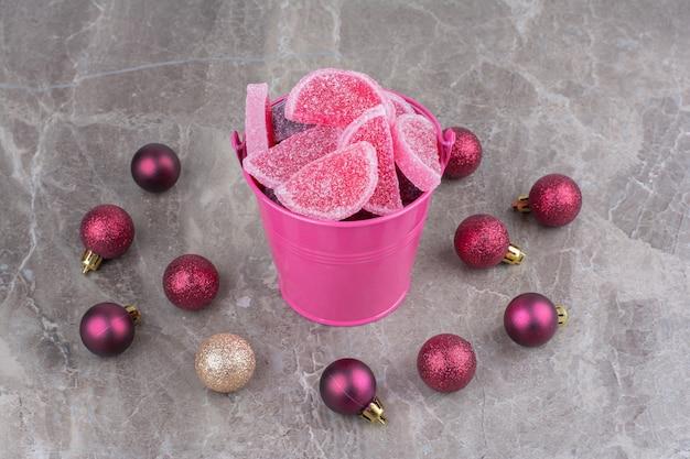 대리석 배경에 빨간색 크리스마스 볼 달콤한 마멀레이드의 전체 핑크 양동이. 무료 사진
