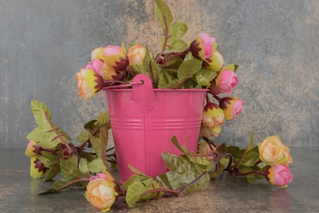 大理石の表面に花束が付いたピンクのバケツ。 無料写真
