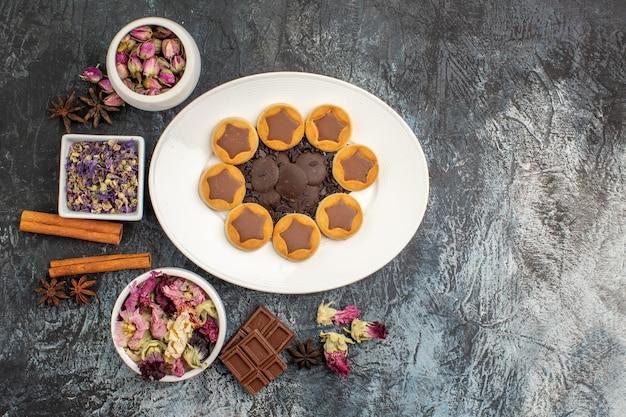 灰色の地面にドライフラワーとチョコレートバーのさまざまなボウルと各種クッキーのプレート 無料写真
