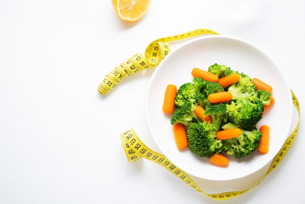 ダイエット食品、ゆで野菜、ブロッコリー、にんじん、フィットネス栄養、コピースペース、上面図のプレート Premium写真
