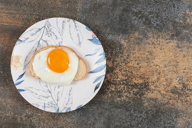 Тарелка с яйцом на ломтике белого хлеба. Бесплатные Фотографии