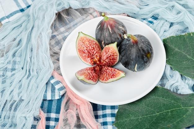 青とピンクのテーブルクロスが付いた全体とスライスされた黒いイチジクのプレート。 無料写真