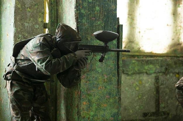 Игрок играет в пейнтбол с ружьем. фото высокого качества Бесплатные Фотографии