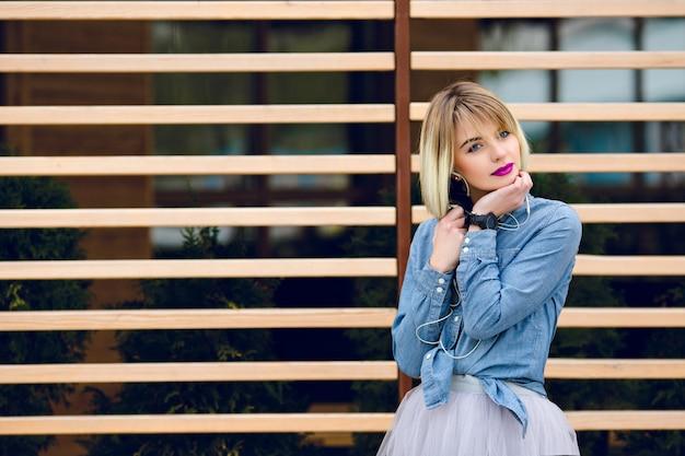 明るいピンクの唇と後ろに縞模様の木製の白頭が付いているスマートフォンで音楽を聴くヌードメイクで夢のようなブロンドの女の子の肖像画 無料写真