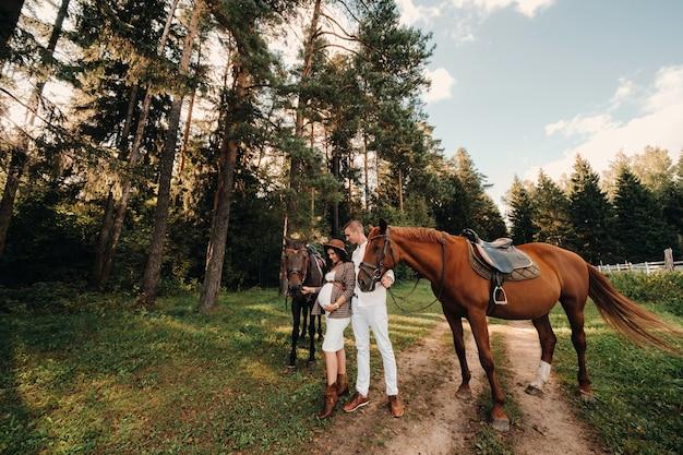 自然の森の馬の横に帽子をかぶった妊婦と白い服を着た夫が立っている。馬を持った男とスタイリッシュな妊婦。家族。 Premium写真