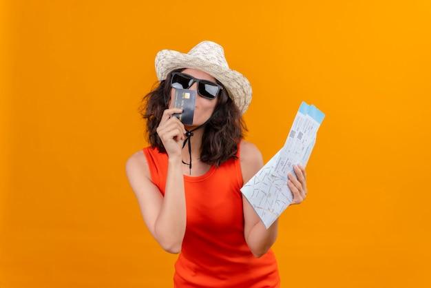 日よけ帽とサングラスを身に着けているオレンジ色のシャツを着た短い髪のかなり若い女性がクレジットカードにキスする地図と飛行機のチケットを持っています 無料写真