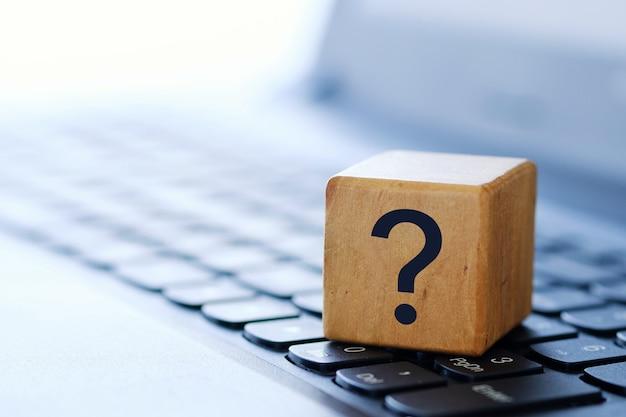 Вопросительный знак на деревянном кубе на клавиатуре компьютера с размытым фоном и малой глубиной резкости. Premium Фотографии