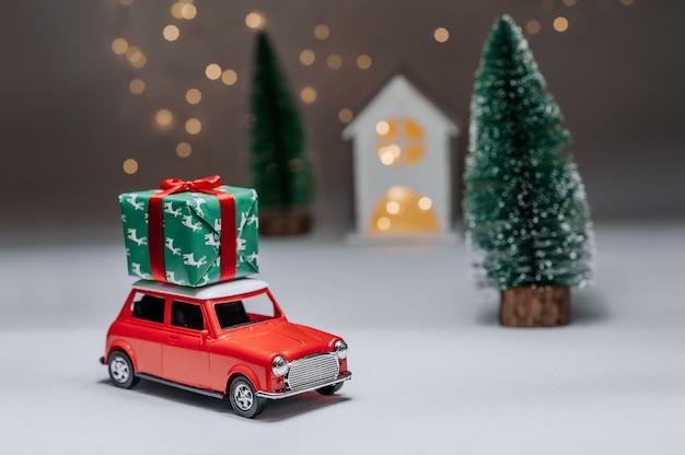숲과 집의 배경에 빨간 차가 크리스마스 새해 선물을 가져올 것입니다. 프리미엄 사진