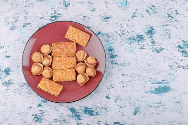 クラッカーと練乳のショートブレッドナッツの赤いプレート。 無料写真
