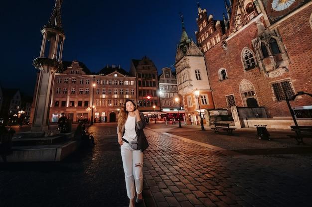 ロマンチックな女の子が夜遅くにヴロツワフの旧市街を歩きます。ポーランドの旧市街でズボンとジャケットを着た女性の散歩。 Premium写真