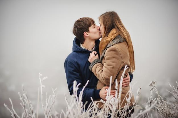 Романтическая влюбленная пара гуляет в снежном парке. зимние каникулы. мужчина и женщина обнимаются и целуются, наслаждаясь прогулкой. Premium Фотографии