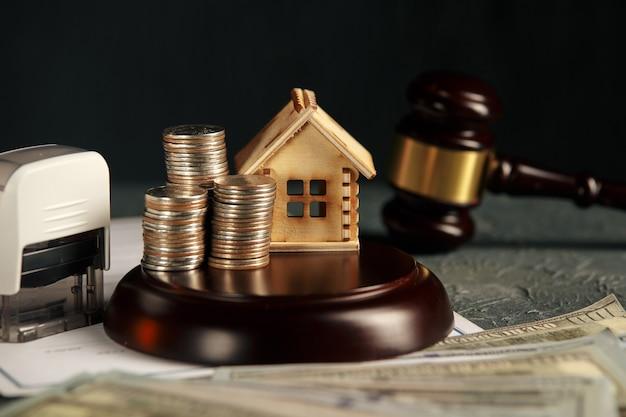 Ряд монет на модели небольшого дома и молоток законного аукциона Premium Фотографии