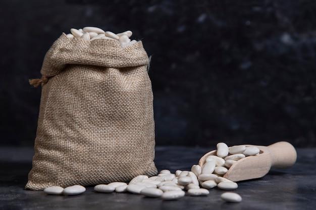 돌 위에 놓인 마른 버터 콩으로 가득 찬 자루 가방 무료 사진