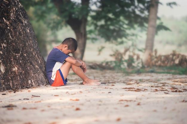 a sad boy sitting with tree photo premium download
