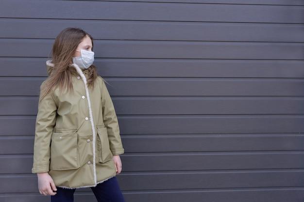 Грустная маленькая девочка в медицинской маске на улице смотрит в сторону Premium Фотографии