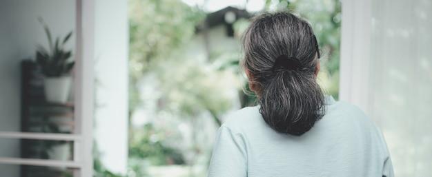 Грустная пожилая женщина смотрит в окно Premium Фотографии