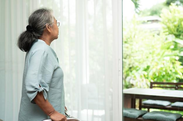 Грустная пожилая женщина использует ходунки, чтобы стоять перед окнами, смотреть на улицу и чувствовать себя одинокой. Premium Фотографии