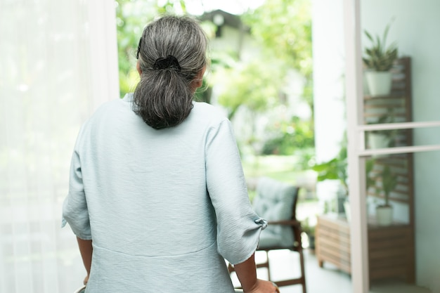 Грустная пожилая женщина использует уокера, чтобы стоять перед окнами, смотреть на улицу и чувствовать себя одиноким. Premium Фотографии