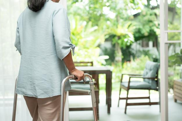 Грустная пожилая женщина использует уокера, чтобы стоять перед окнами Premium Фотографии