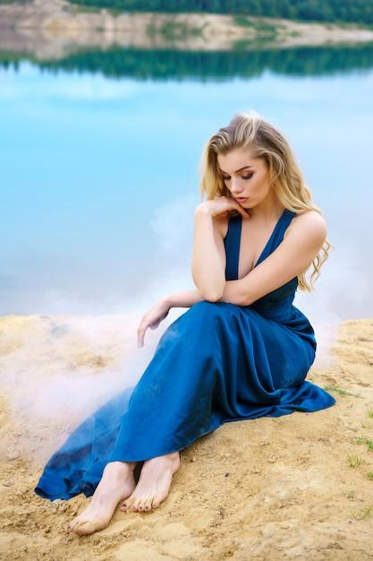 青い長いドレスを着た悲しい若い美しい女性は湖の岸に一人で座っています。 Premium写真