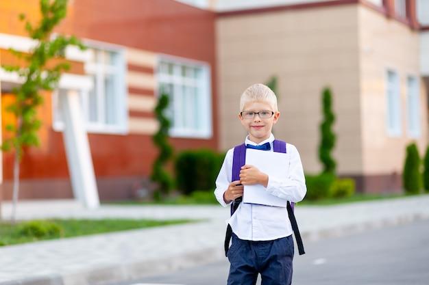 バックパックと白い本と眼鏡をかけた男子生徒が学校に立っています Premium写真