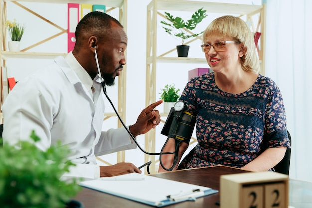 クリニックでセラピストを訪ねる年配の女性 無料写真