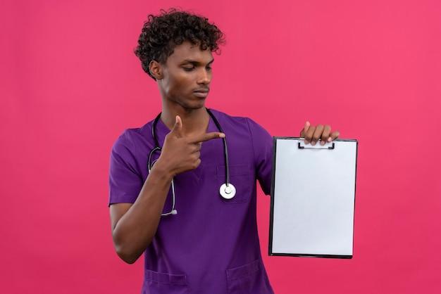 空白の紙のシートを使用してクリップボードで人差し指で指している聴診器で紫の制服を着た巻き毛の深刻な若いハンサムな浅黒い医者 無料写真