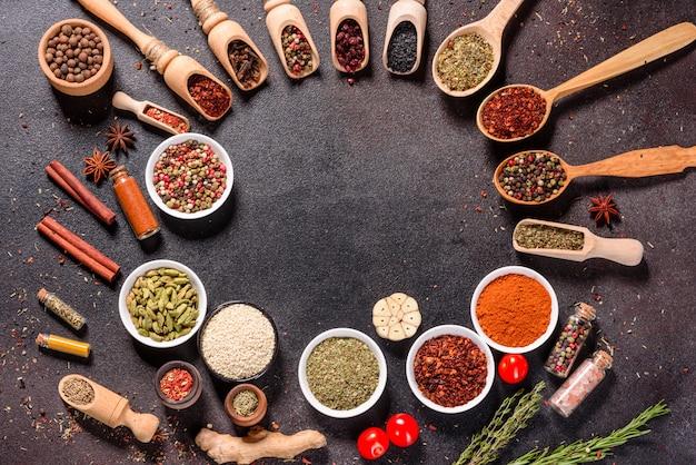スパイスとハーブのセット。インド料理。コショウ、塩、パプリカ、バジル。上面図。 Premium写真