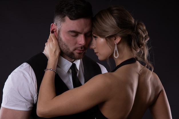 Сексуальная девушка со светлыми волосами поглаживает щеку своего мужчины, лукаво подсматривая, насколько ему это действительно нравится Premium Фотографии