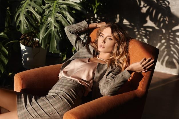 ビジネススーツのセクシーな若い女性は、彼女の後ろの壁に植物からの影が付いているオフィスの肘掛け椅子にかかっています。シャドウオーバーレイ効果。市松模様のスーツのモデルの女の子が肘掛け椅子に座っています。 Premium写真