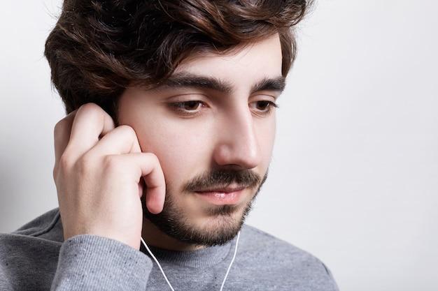 ひげと口ひげを見下ろす魅力的な若い男の横向きの肖像画 Premium写真