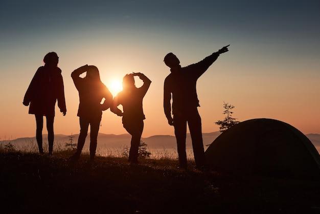 Силуэт группы людей веселятся на вершине горы возле палатки во время заката. Бесплатные Фотографии